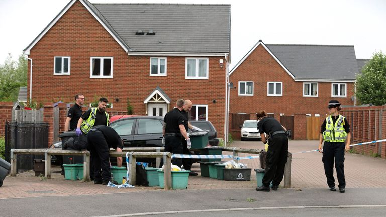 Police officers search recycling bins at the scene in Dexter Way, Gloucester