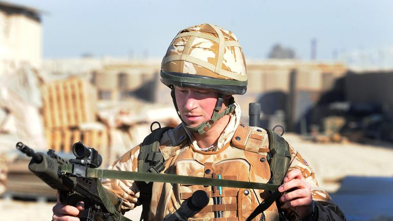 Prince Harry holds his SA80 as he prepares to patrol through the deserted town of Garmsir