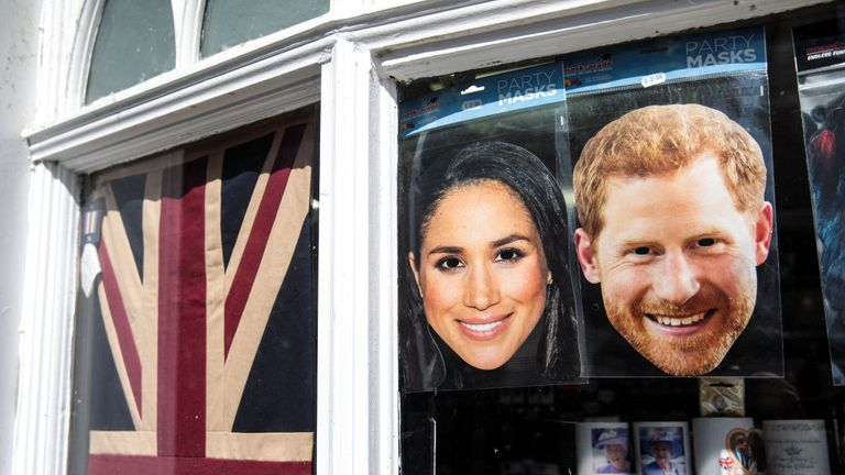 Masks of Prince Harry and his fiance US actress Meghan Markle sit in the window of a gift shop on May 10, 2018 in Windsor