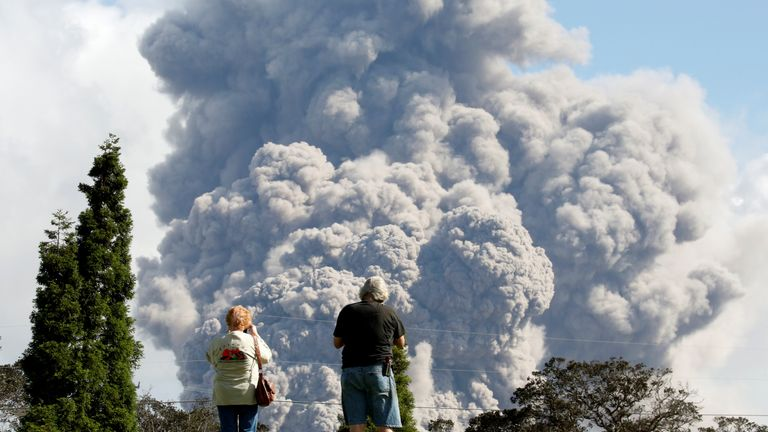 People watch ash erupt from the Halemaumau Crater near the community of Volcano