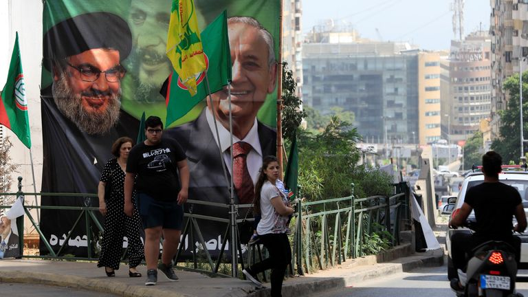 People walk past a campaign banner showing Lebanese Parliament Speaker and candidate for parliamentary election Nabih Berri and Hezbollah leader Sayyed Hassan Nasrallah in Beirut, Lebanon May 4, 2018. REUTERS/Jamal Saidi