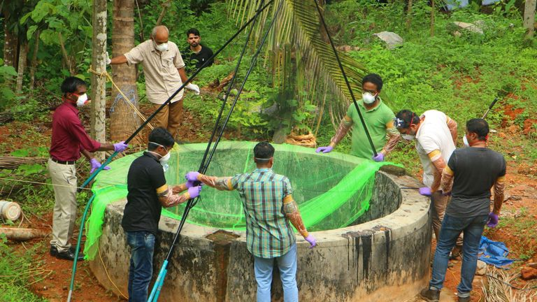 Kerala officials inspect a well to look for infected bats