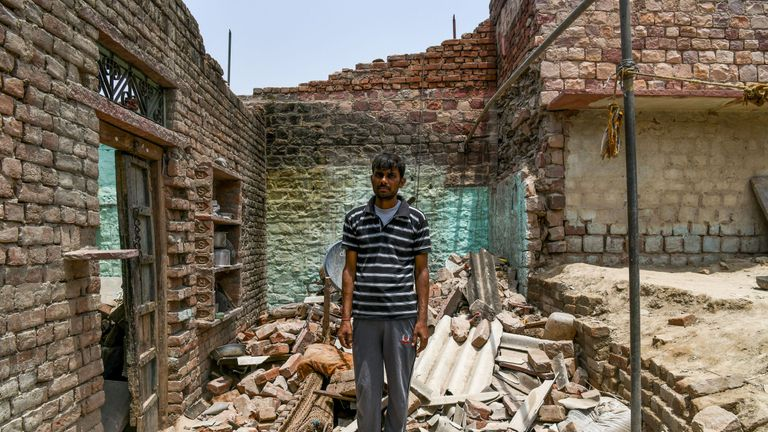 A man stands in the ruins of his house which was destroyed in the storms earlier this month