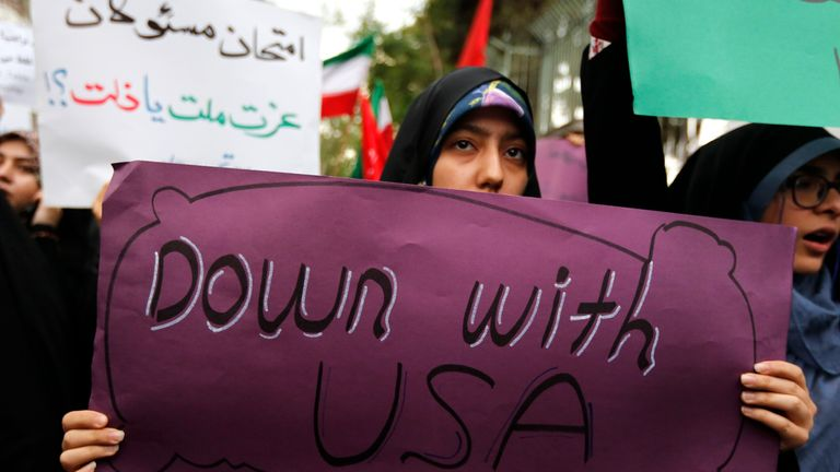 Iranian women carry anti-US signs during a demonstration outside the former US embassy headquarters in the capital Tehran