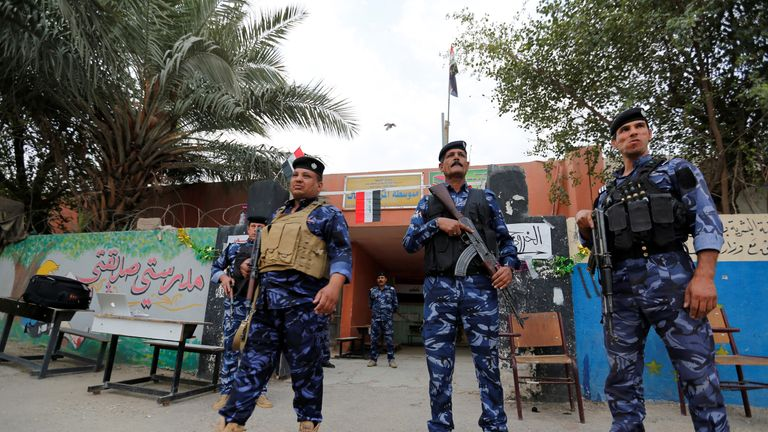 Iraqi security forces stand guard outside a polling station in Baghdad