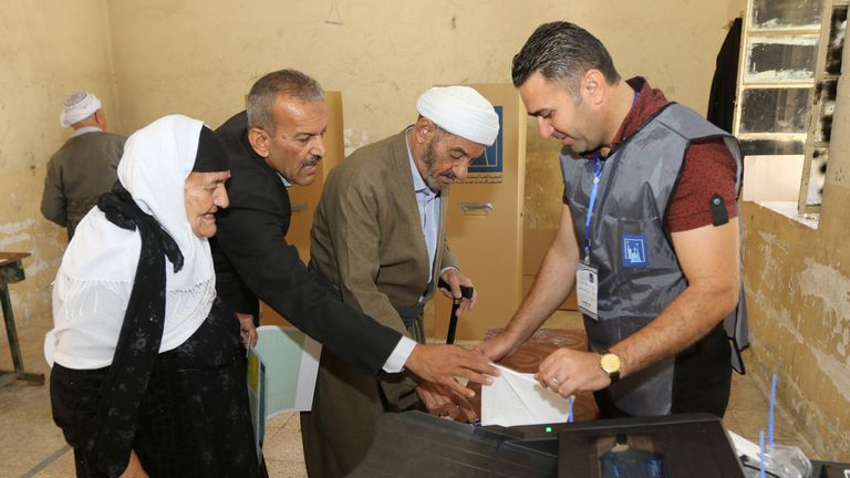 People prepare to cast their vote at a polling station in Kirkuk