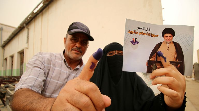 People show their ink-stained fingers after voting in Basra