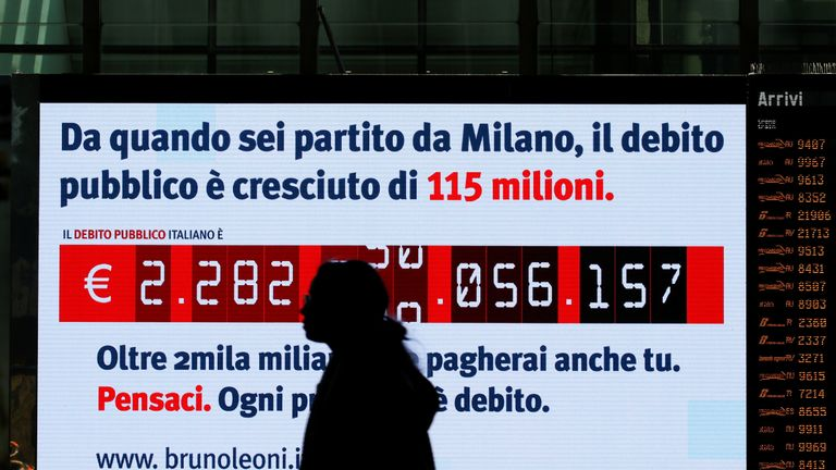 """A woman walks past a """"debt clock"""" screen, installed by Bruno Leoni Institute's analysts, displaying Italy's public debt at the Termini central station in Rome, Italy February 15, 2018"""