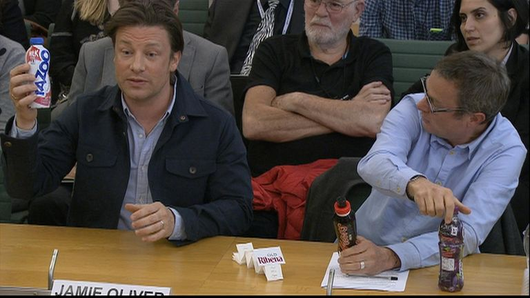 Jamie Oliver holds up a drink bottle to demonstrate the sugar levels while giving evidence to MPs