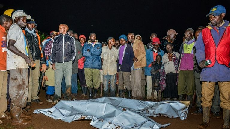 Rescuers and locals stand around two recovered bodies after the flooding