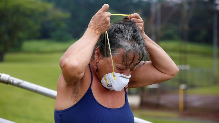 A resident puts on a dust mask to protect herself from volcanic emissions