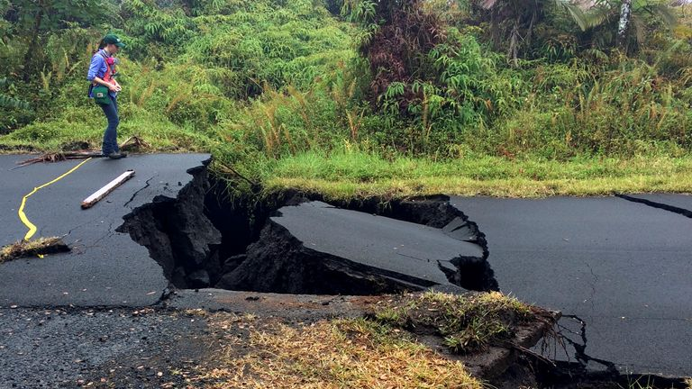 A geologist inspects cracks on a road following the eruption of Kilauea volcano