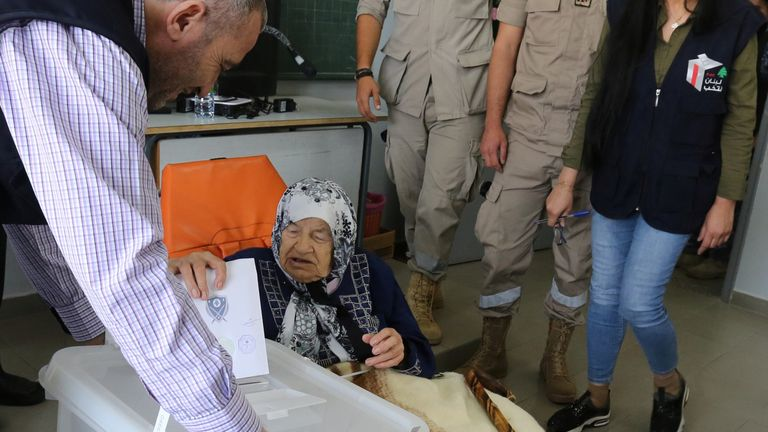 An elderly woman casts her vote