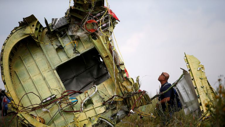 A Malaysian air crash investigator inspects the crash site of Malaysia Airlines Flight MH17, near the village of Hrabove (Grabovo) in Donetsk region, Ukraine