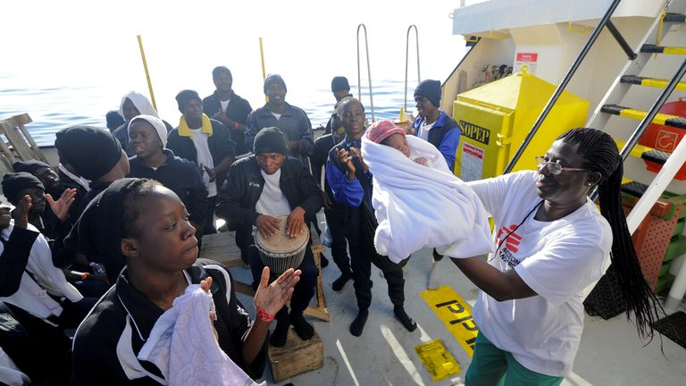 Migrants dance and sing to celebrate the birth of Miracle