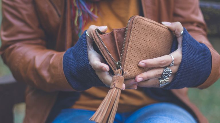 A young woman is holding her wallet outdoors in autumn park in city