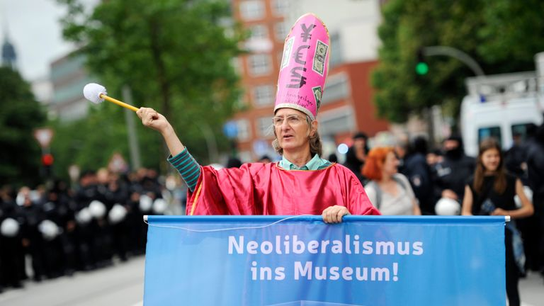 A protester holds a banner reading 'Neoliberalism in the Museum' during the 'Solidarity without borders instead of G20' demonstration on July 8, 2017 in Hamburg