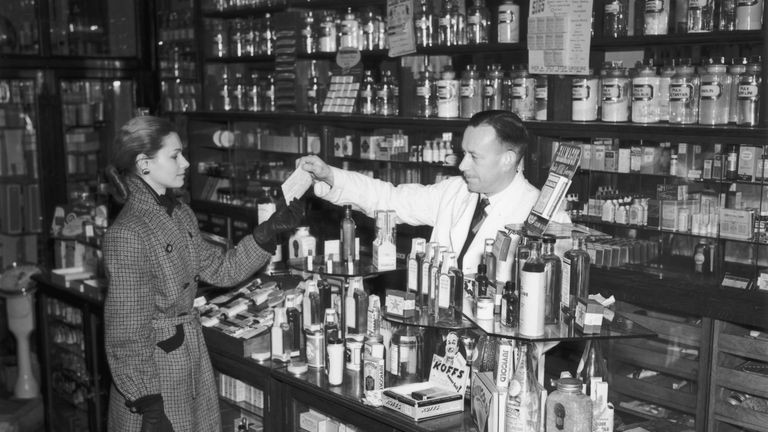 A woman hands over a prescription in a chemist's shop in Fleet Street, London