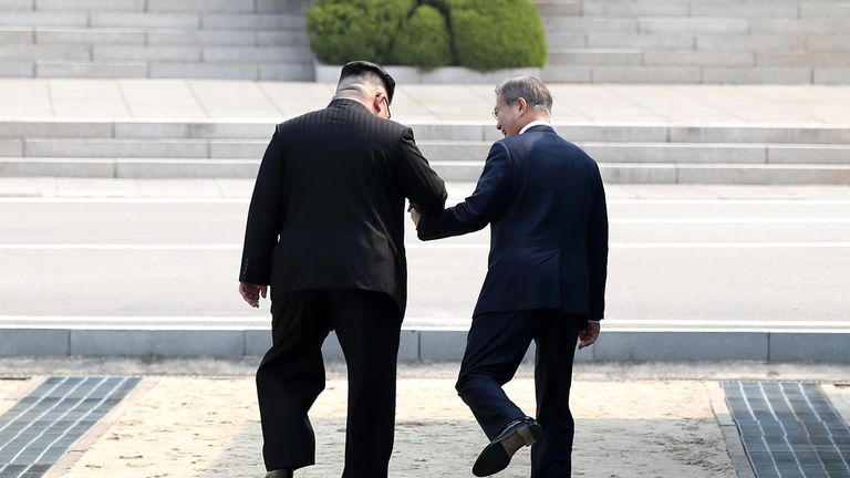 Kim Jong Un (L) takes hand of Moon Jae-in (R) to cross the demarcation line