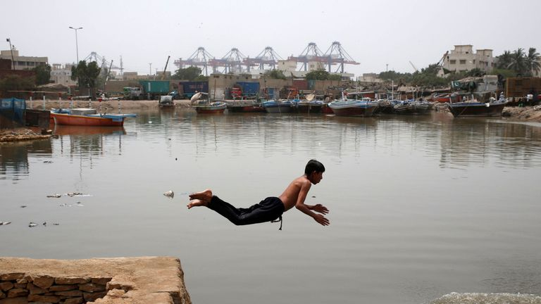 A boy jumps into water in Karachi, Pakistan, amid soaring temperatures
