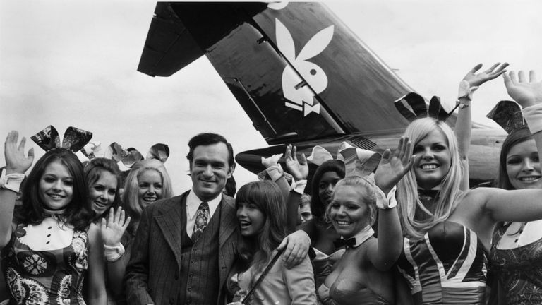 Hugh Hefner stand in front of a plane complete with the iconic Playboy logo