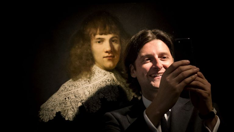 Amsterdam art dealer and historian Jan Six (R) takes a 'selfie' as he stands beside 'Portrait of a Young Gentleman' by Rembrandt van Rijn