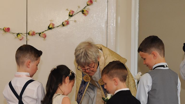 Luna and Alfie exchange rings as the vicar presides over the ceremony