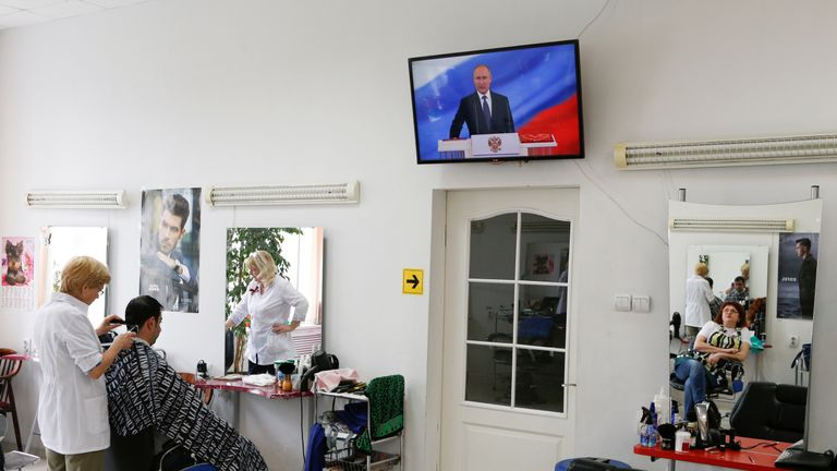 A hairdresser, who watches a ceremony to inaugurate Vladimir Putin as President of Russia, is reflected in a mirror at a hair design salon in Stavropol, Russia May 7, 2018. REUTERS/Eduard Korniyenko