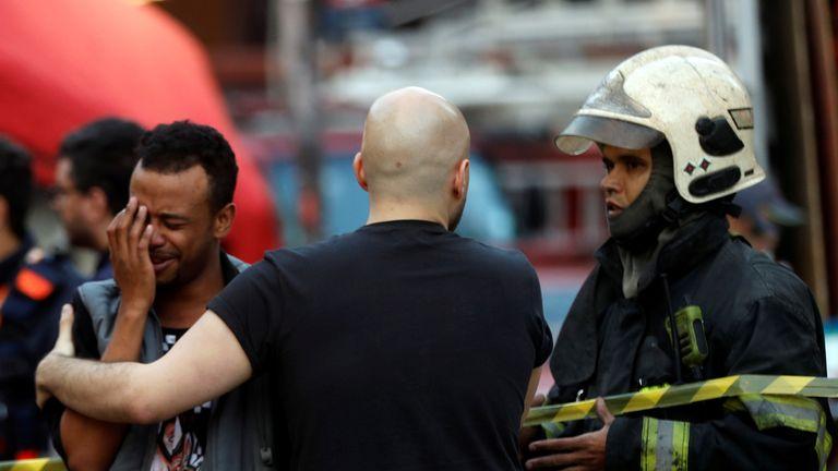 Firefighter comfort a man near the site