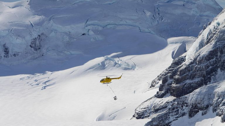 A helicopter distributing bait over an ice cap in South Georgia