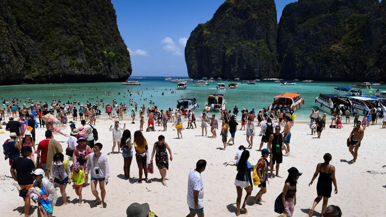 This photo taken on April 9, 2018 shows a crowd of tourists on the Maya Bay beach, on the southern Thai island of Koh Phi Phi. Across the region, Southeast Asia's once-pristine beaches are reeling from decades of unchecked tourism as governments scramble to confront trash-filled waters and environmental degradation without puncturing a key economic driver. / AFP PHOTO / Lillian SUWANRUMPHA / TO GO WITH AFP STORY 'THAILAND-INDONESIA-PHILIPPINES-TOURISM-ENVIRONMENT' by Lillian SUWANRUMPHA with Joe