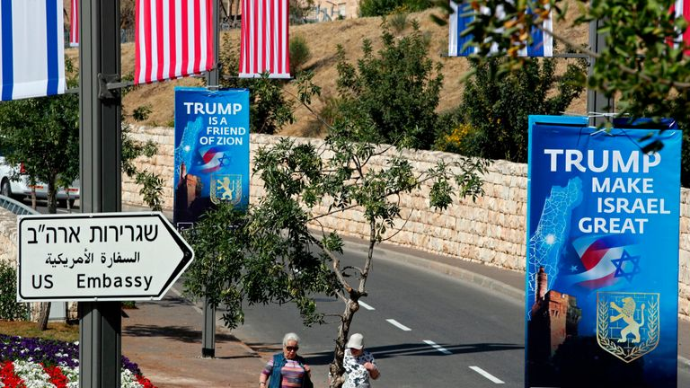 People walk on May 11, 2018 near the compound of the US consulate in Jerusalem, which will host the new US embassy, as posters praising the US president hang in the street