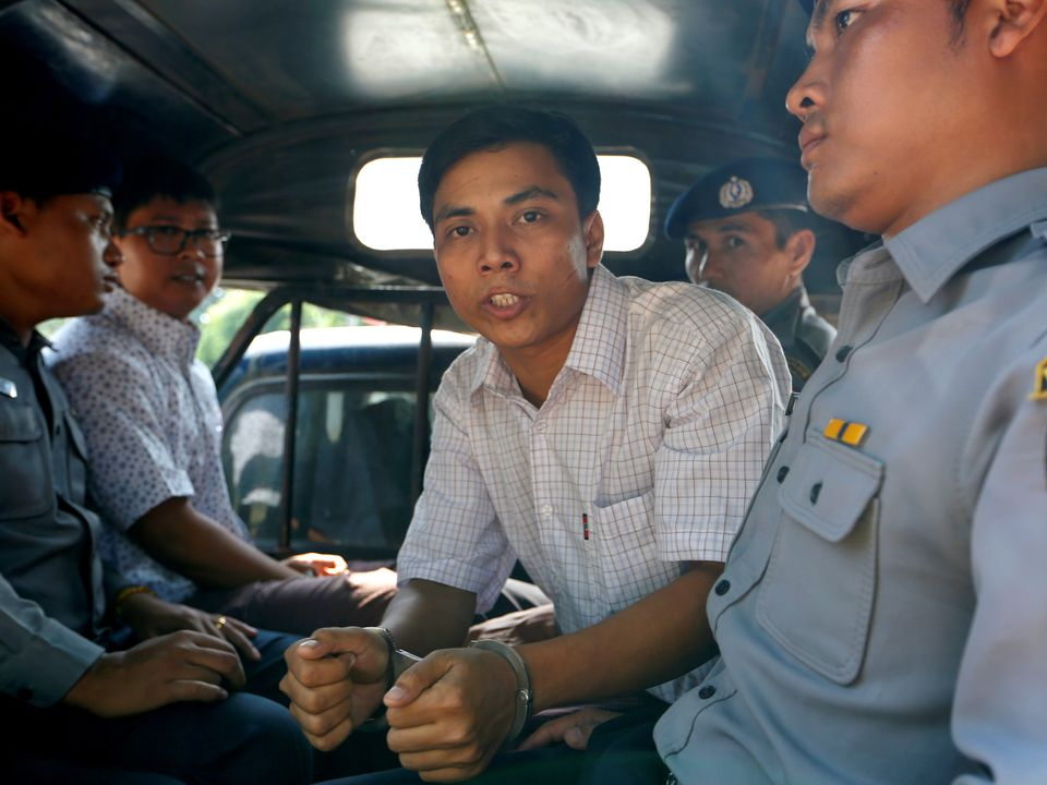 Detained Reuters journalist Kyaw Soe Oo (R) and Wa Lone (L) are transport in a police vehicle after a court hearing...