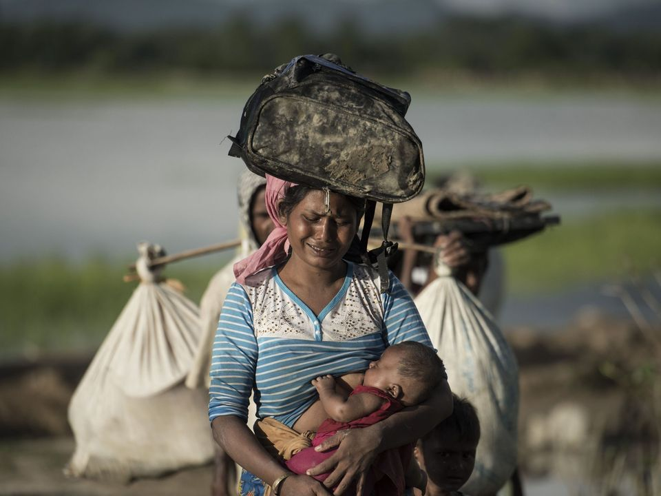 PSHOT - Rohingya refugee cries as she walks after crossing the Naf river from Myanmar into Bangladesh in Whaikhyang on October 9, 2017. A top UN official said on October 7 Bangladesh's plan to build the world's biggest refugee camp for 800,000-plus Rohingya Muslims was dangerous because overcrowding could heighten the risks of deadly diseases spreading quickly. The arrival of more than half a million Rohingya refugees who have fled an army crackdown in Myanmar's troubled Rakhine state since Augu