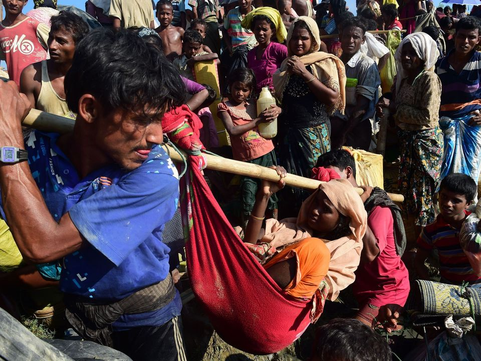 Rohingya refugees carry a woman after crossing the Naf River as they flee violence in Myanmar to reach Bangladesh in Palongkhali near Ukhia on October 16, 2017. The UN has said that 537,000 Rohingya have arrived in Bangladesh over the last seven weeks. They are fleeing violence in Myanmar's Rakhine state, where the United Nations has accused troops of waging an ethnic cleansing campaign against them. / AFP PHOTO / MUNIR UZ ZAMAN (Photo credit should read MUNIR UZ ZAMAN/AFP/Getty Images)