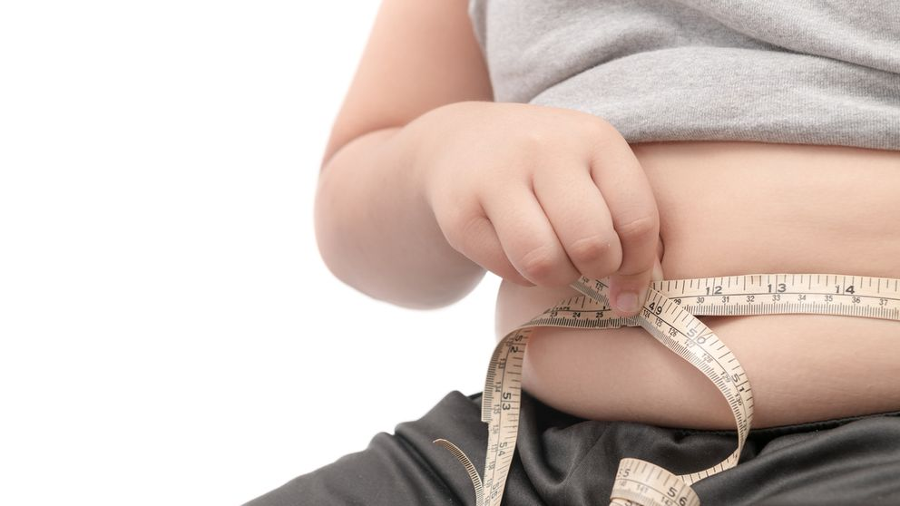 fat child check out his body fat with measuring tape isolated on white background, obesity or diet concept