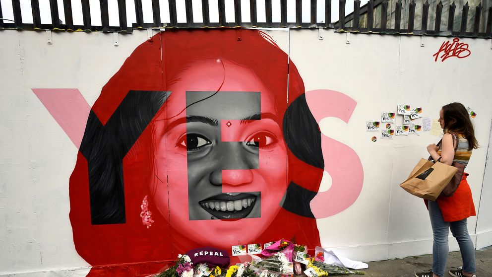 A woman looks at a new mural of Savita Halappanavar with flowers placed beneath it put up on the day of the Abortion Referendum