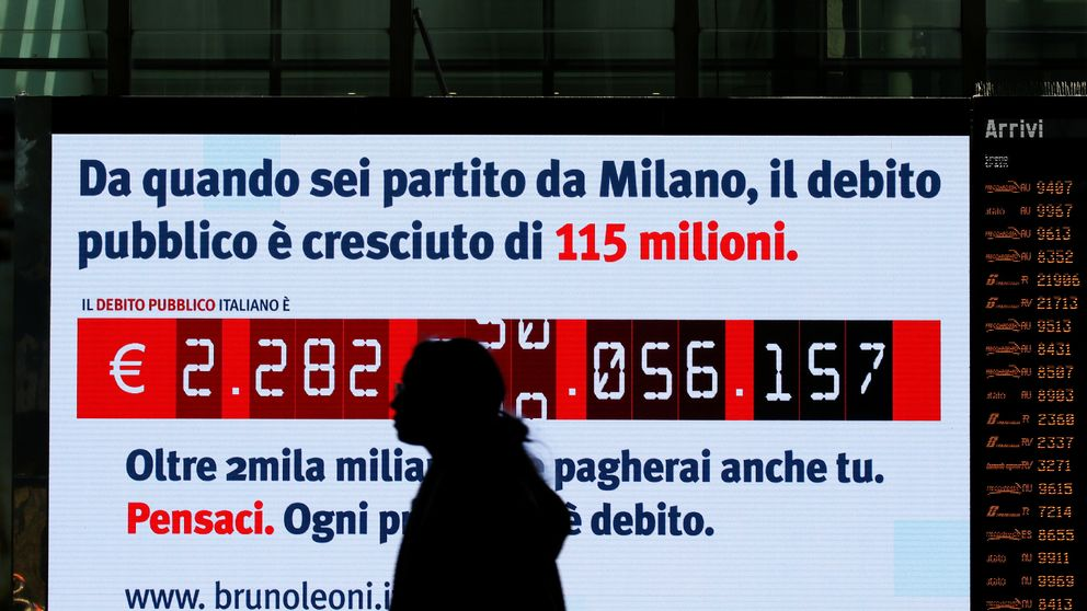 "A woman walks past a ""debt clock"" screen, installed by Bruno Leoni Institute's analysts, displaying Italy's public debt at the Termini central station in Rome, Italy February 15, 2018"