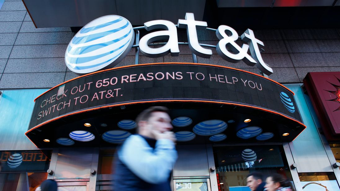People walk past an AT&T store in New York on October 23, 2016