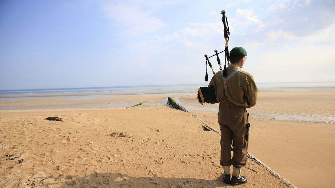 A re-enactor plays the bagpipes on Sword beach as dozens of veterans travelled to Normandy 71 years after D-Day