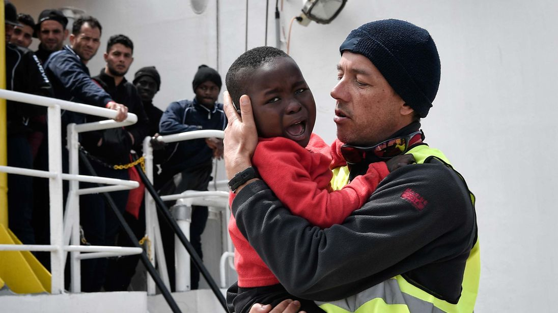 A helper from Doctors Without Borders holds a Nigerian child as he and his mother disembark from the MV Aquarius upon its arrival at the Sicilian port of Messina last month