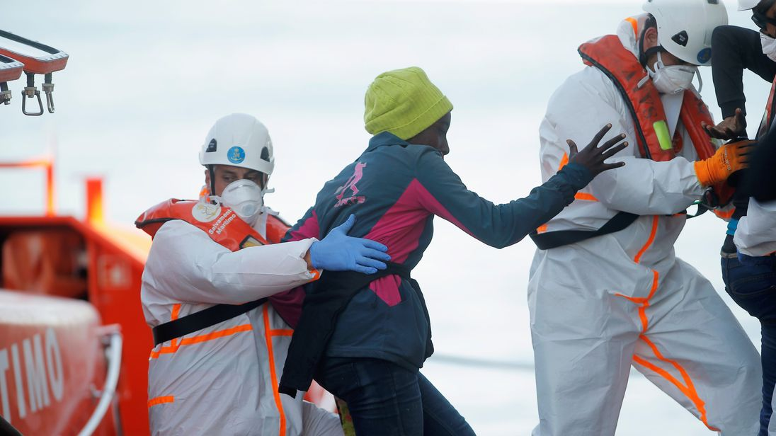 A migrant is helped off a rescue boat at the Spanish port of Malaga