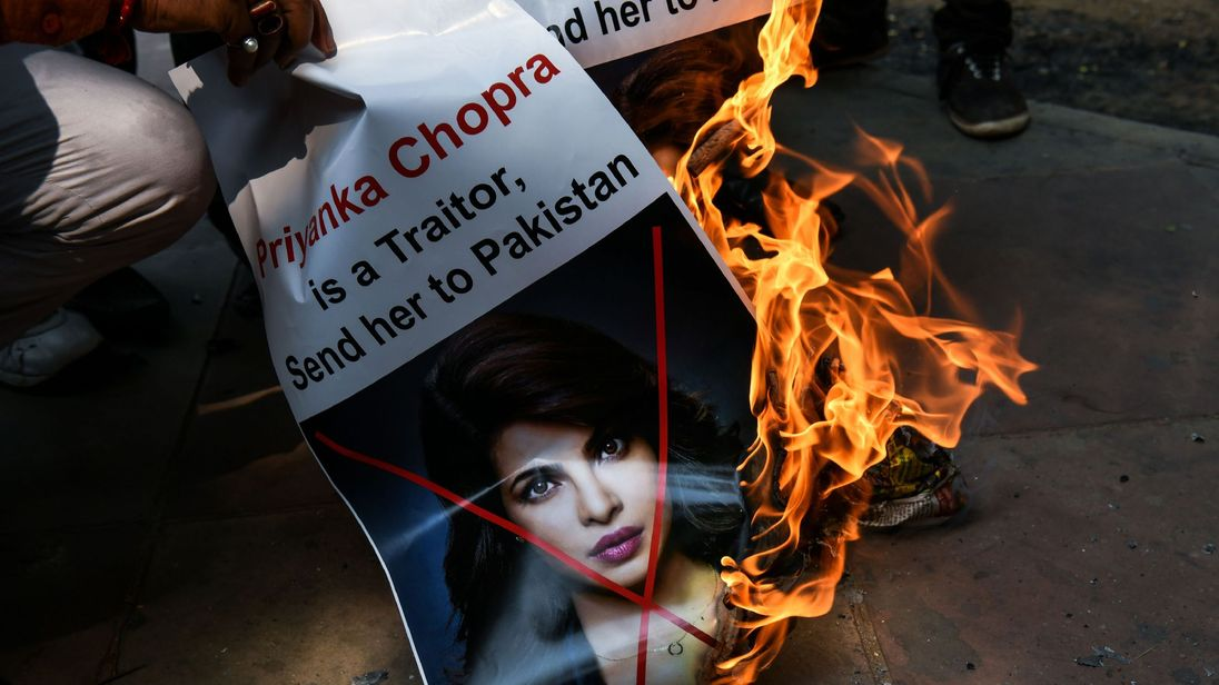 A burning poster describing Chopra as a traitor