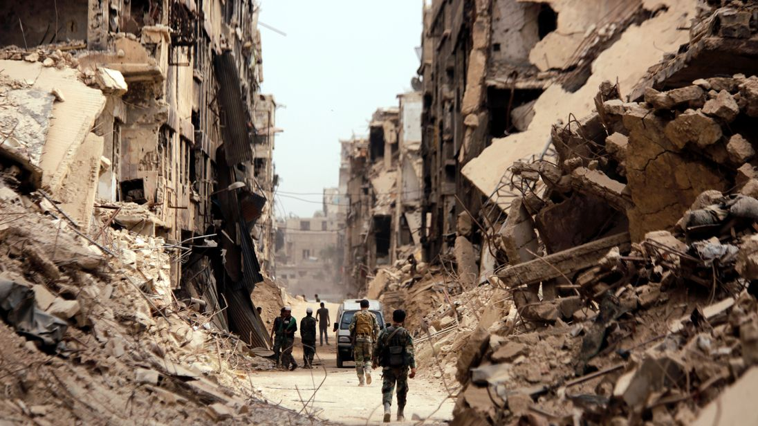 Soldiers walk past damaged buildings in Damascus last month. File pic