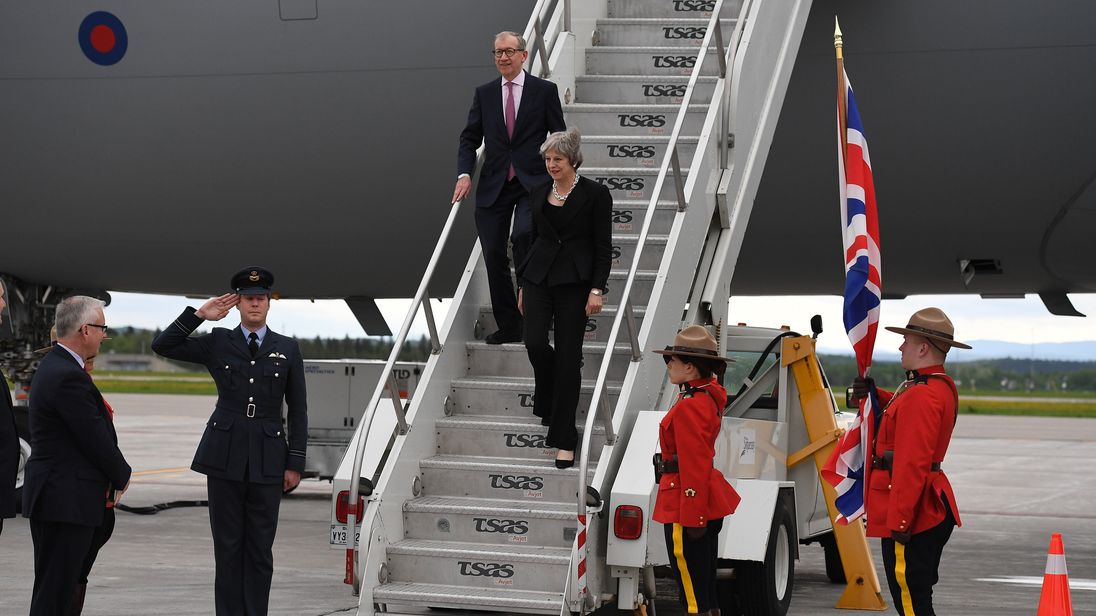 Theresa May and her husband Philip are greeted as they step off the plane in Canada