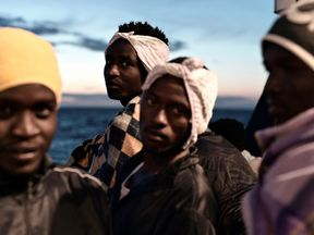 Migrants are seen as they stand on the deck of MV Aquarius, a search and rescue ship run in partnership between SOS Mediterranee and Medecins Sans Frontieres on their way to Spain June 14, 2018. Picture taken June 14, 2018. Karpov / SOS Mediterranee/handout via REUTERS ATTENTION EDITORS - THIS IMAGE WAS PROVIDED BY A THIRD PARTY.