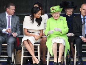 Queen Elizabeth and Meghan sit together at the bridge opening