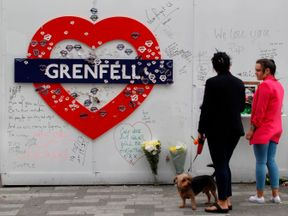 Messages of condolence for the victims of the Grenfell Tower fire are pictured on a fence near to the burned-out shell of the tower