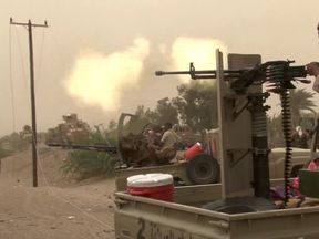 Yemeni pro-government forces fire a heavy machine gun at the south of Hodeida airport