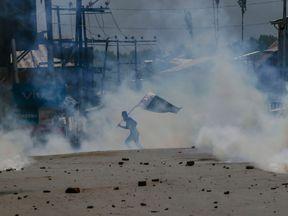 A Kashmiri Muslim protester carries Pakistani flag amid tear gas smoke